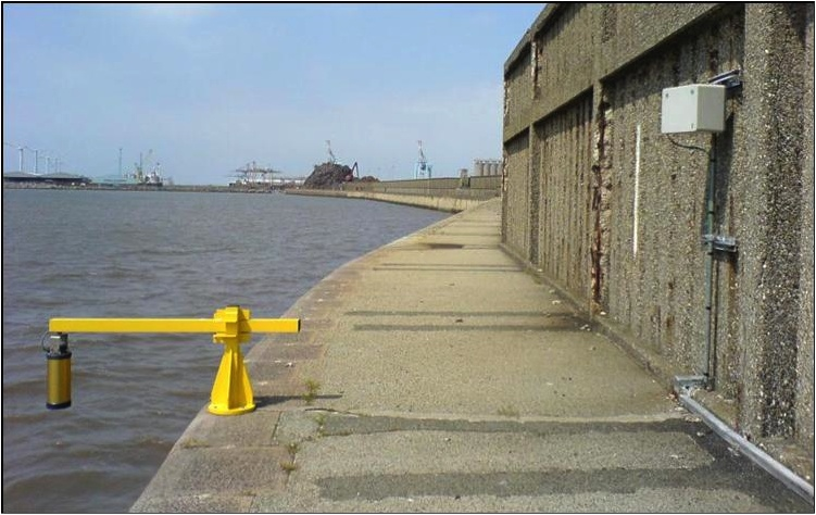 Figure 4. A radar tide gauge at Gladstone Dock in Liverpool. The gold-coloured radar transducer transmits pulses down to the water and so measures sea level. The grey box on the wall is a satellite transmitter that sends the data to the laboratory.
